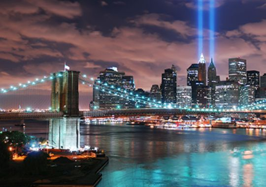 New York City's Manhattan panorama view with the Brooklyn Bridge and office building skyscrapers skyline illuminated over Hudson River in memory of September 11. (Courtesy of Songquan Deng)